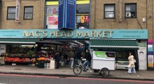 Man rides a cargo bike in front of the Nag's Head Market